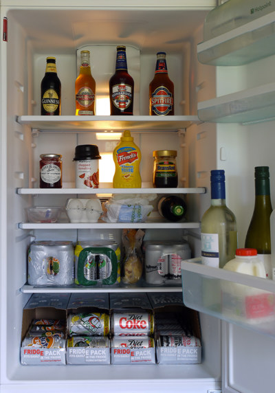 open fridge loaded with assorted drinks and condiments